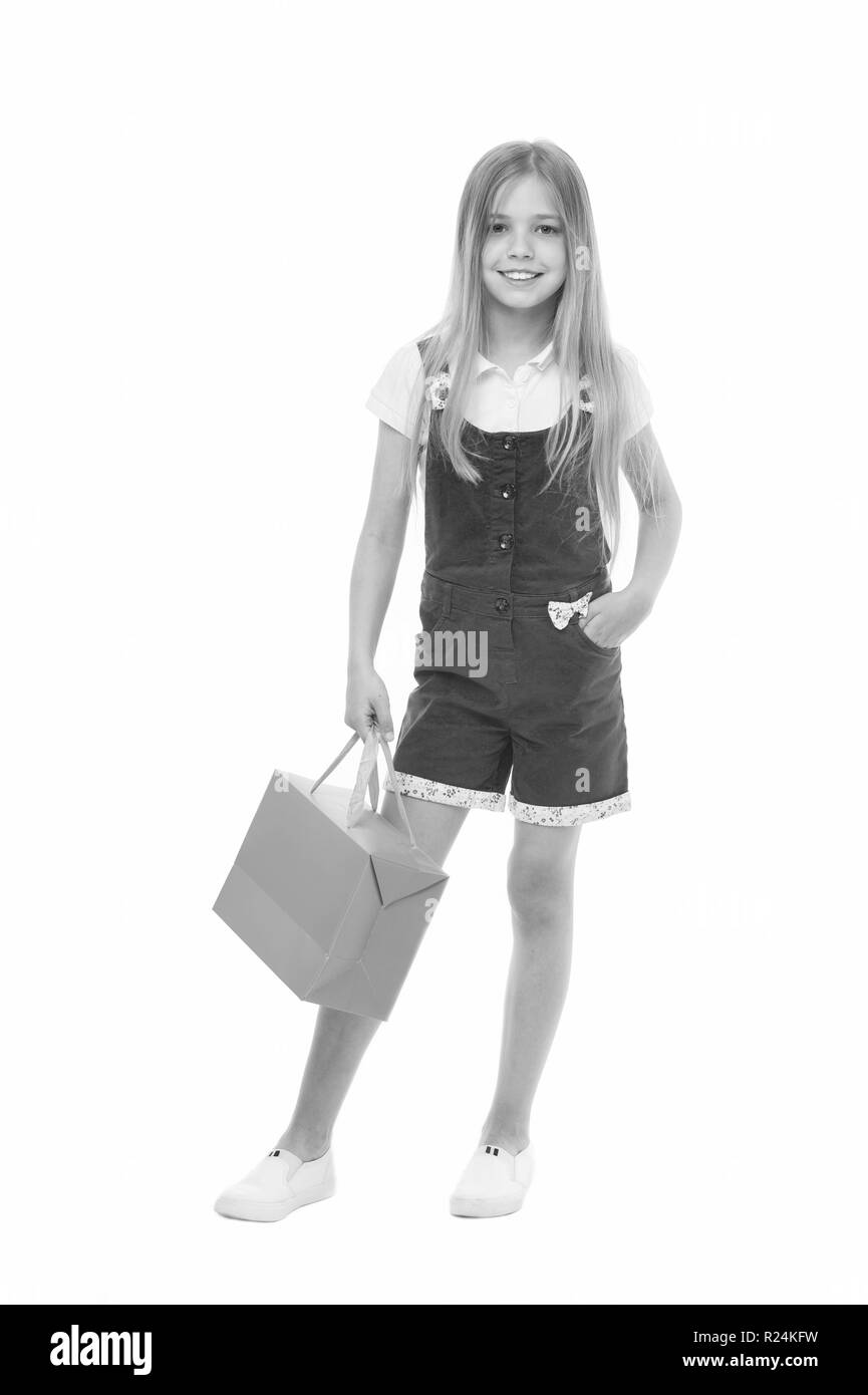 Kids designer clothing summer sale. Girl cute teenager carries shopping bag. Kid bought clothing summer sale. Sale benefits. Seasonal sale concept. Girls absolutely fond of shopping. - Stock Image