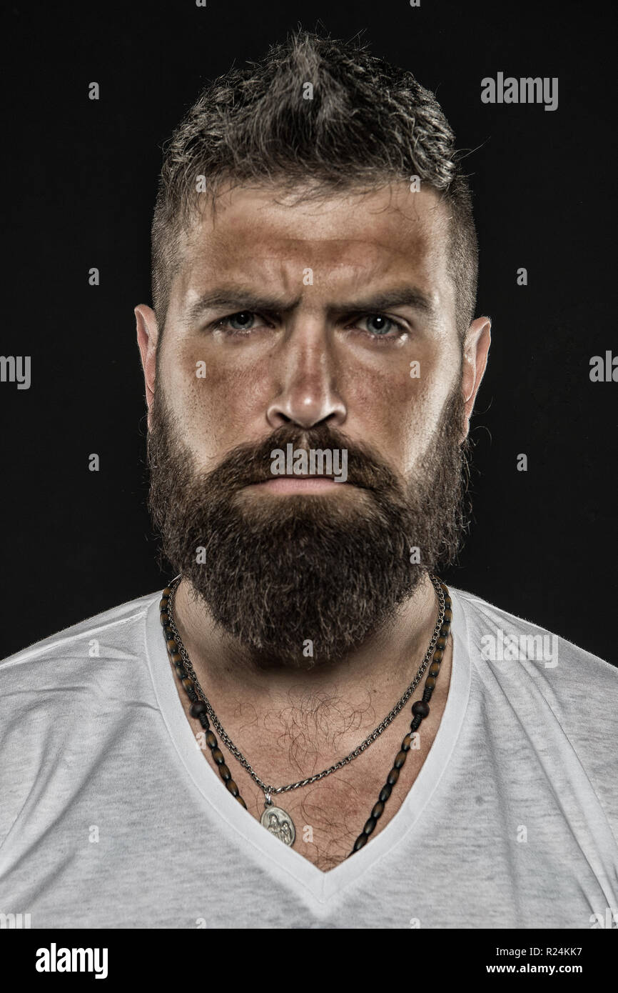 Brutality and masculinity. Man bearded hipster serious face close up. Brutal man with over suntanned skin face. Hipster with beard and mustache looks strict and brutal. Brutal masculine appearance. - Stock Image