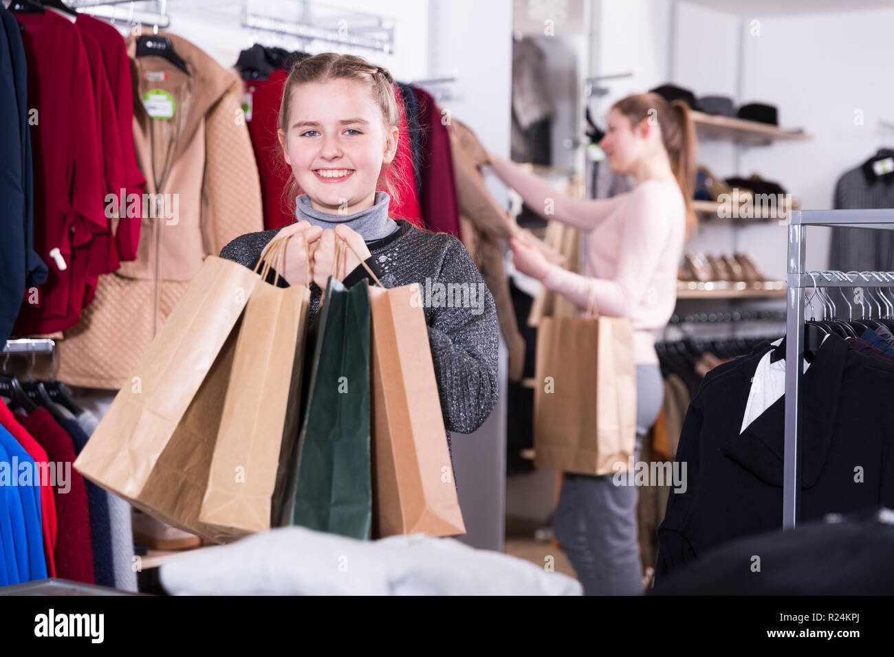 54aa97d47 Happy girl holding many bags after family shopping with mother in modern clothing  store