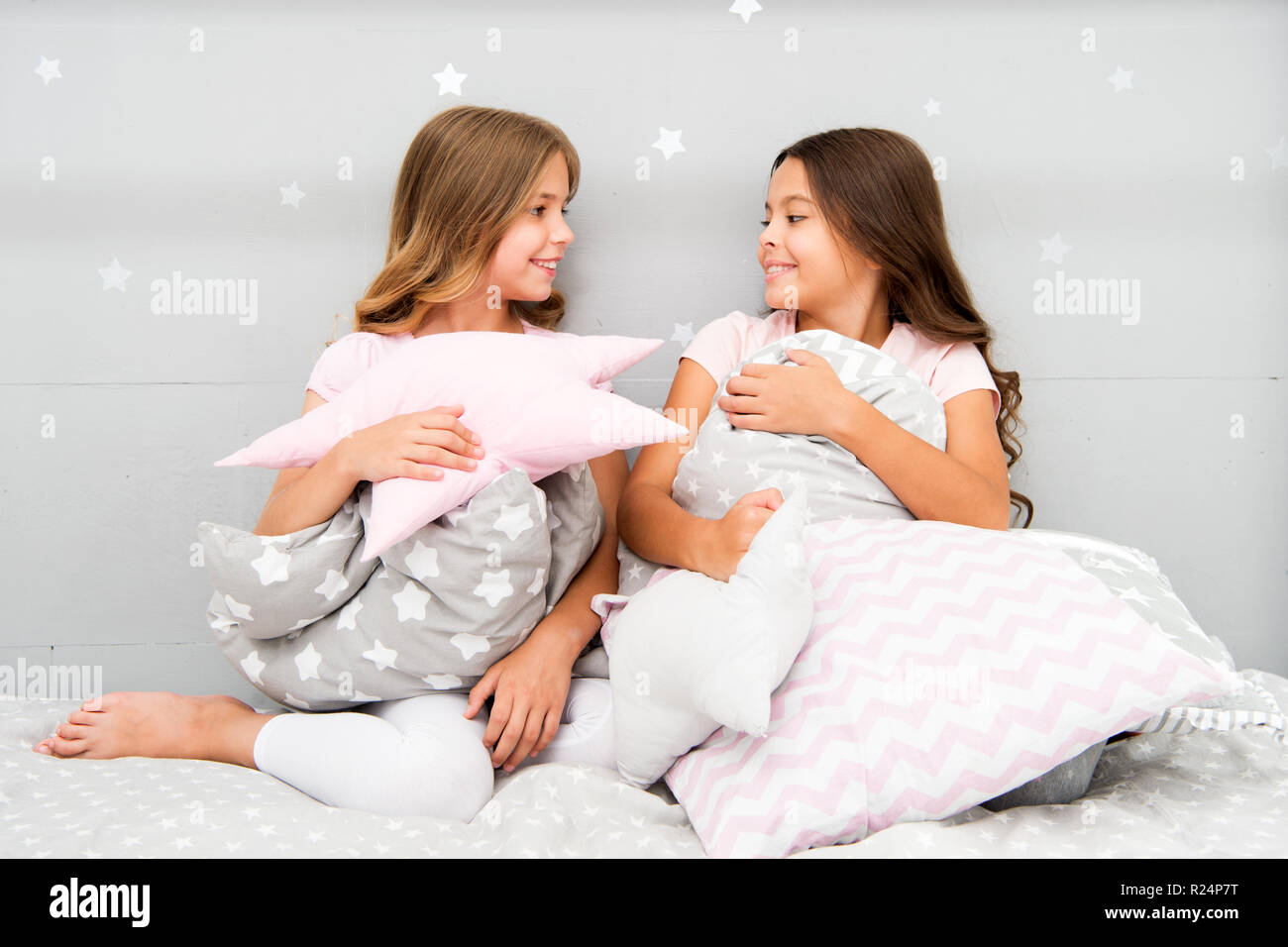 Girls children on bed with cute pillows. Pajamas party concept. Girls just want to have fun. Girlish secrets honest and sincere. Friends kids have nice time pleasant leisure. Best friends forever. - Stock Image