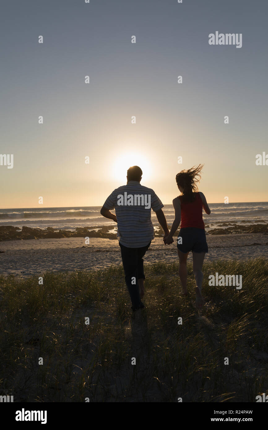 Couple holding hands and running on beach - Stock Image
