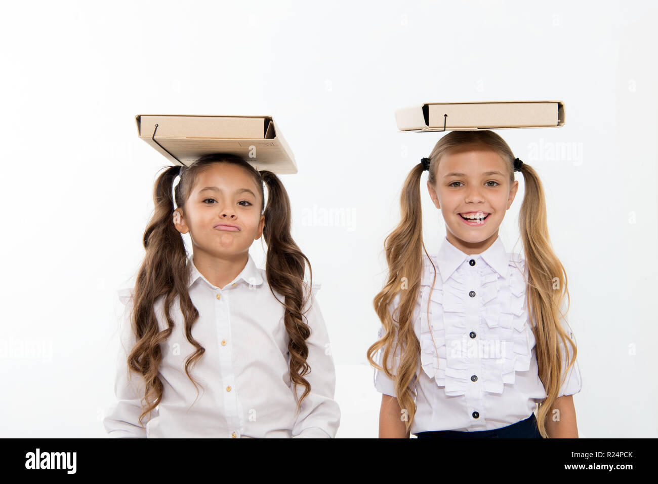 Proper posture. Schoolgirls with cute pony tails hairstyle carry folders on heads. Perfect schoolgirls with tidy fancy hair and proper posture carry folders on heads. Balance and burden of knowledge. - Stock Image