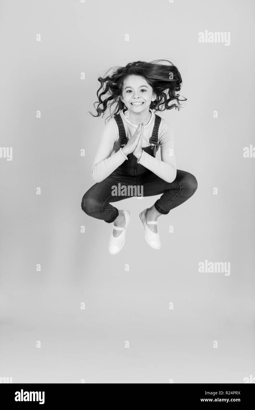 Small girl happy jump in yoga pose, energy. Child with long brunette hair in jeans overall jump, fashion. Meditation, concentration, zen. Fashion, beauty, look. Energy, activity, sport punchy pastel - Stock Image
