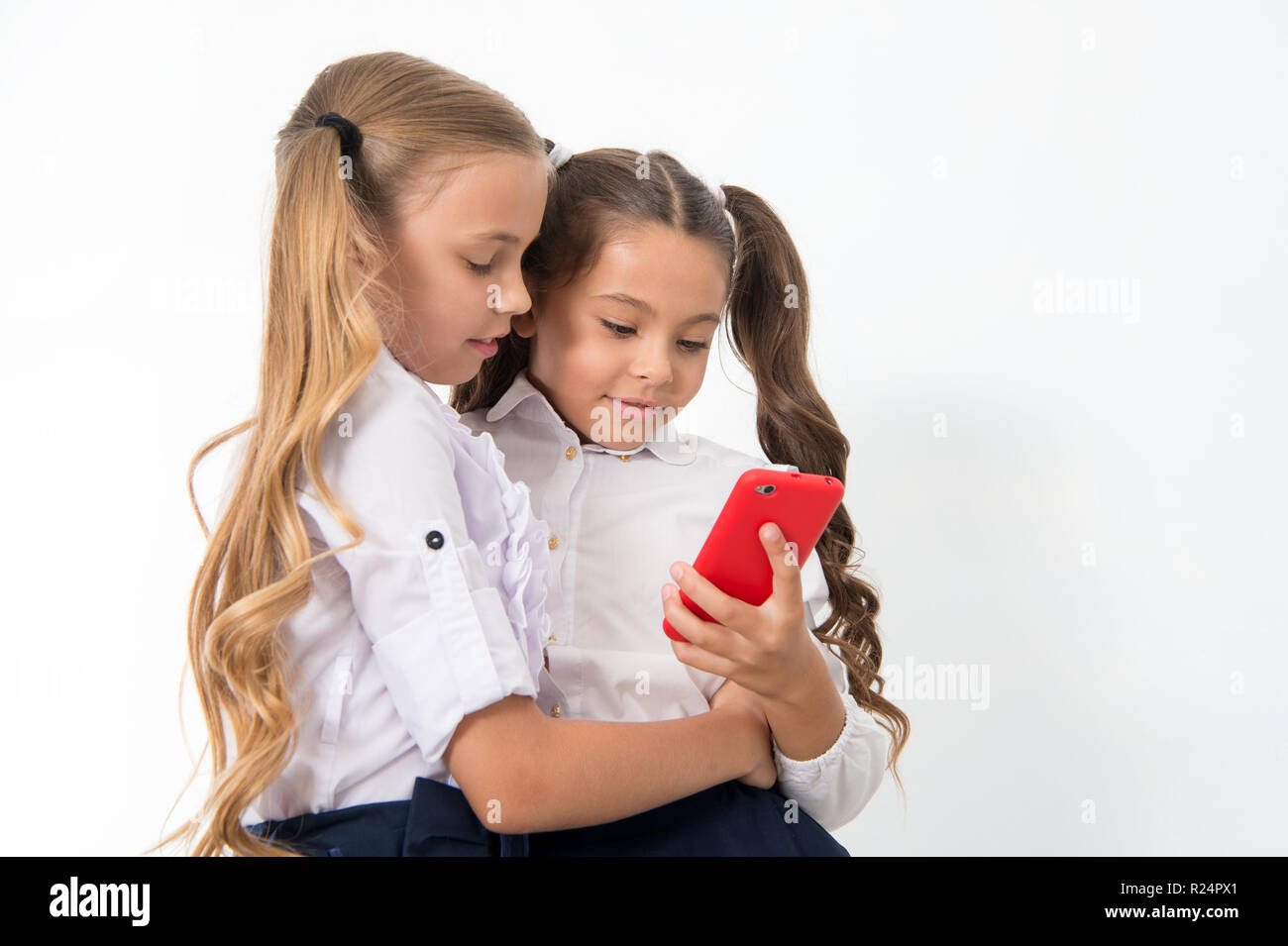 Educational application. Online entertainment concept. Schoolgirls cute pupils use smartphone check social networks. Send message friend. Online communication messaging. Surfing interesting web site. - Stock Image