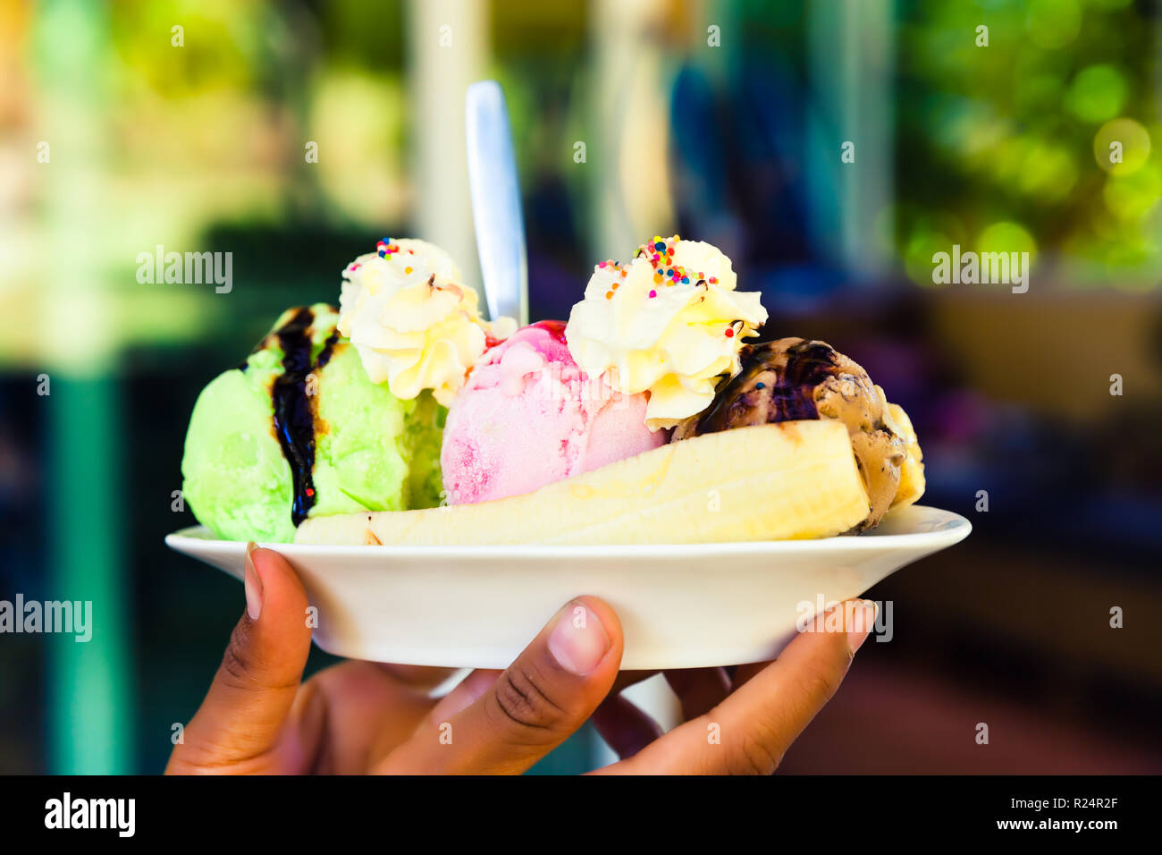 Fresh natural ice cream in woman hand on beautiful blurred background - Stock Image