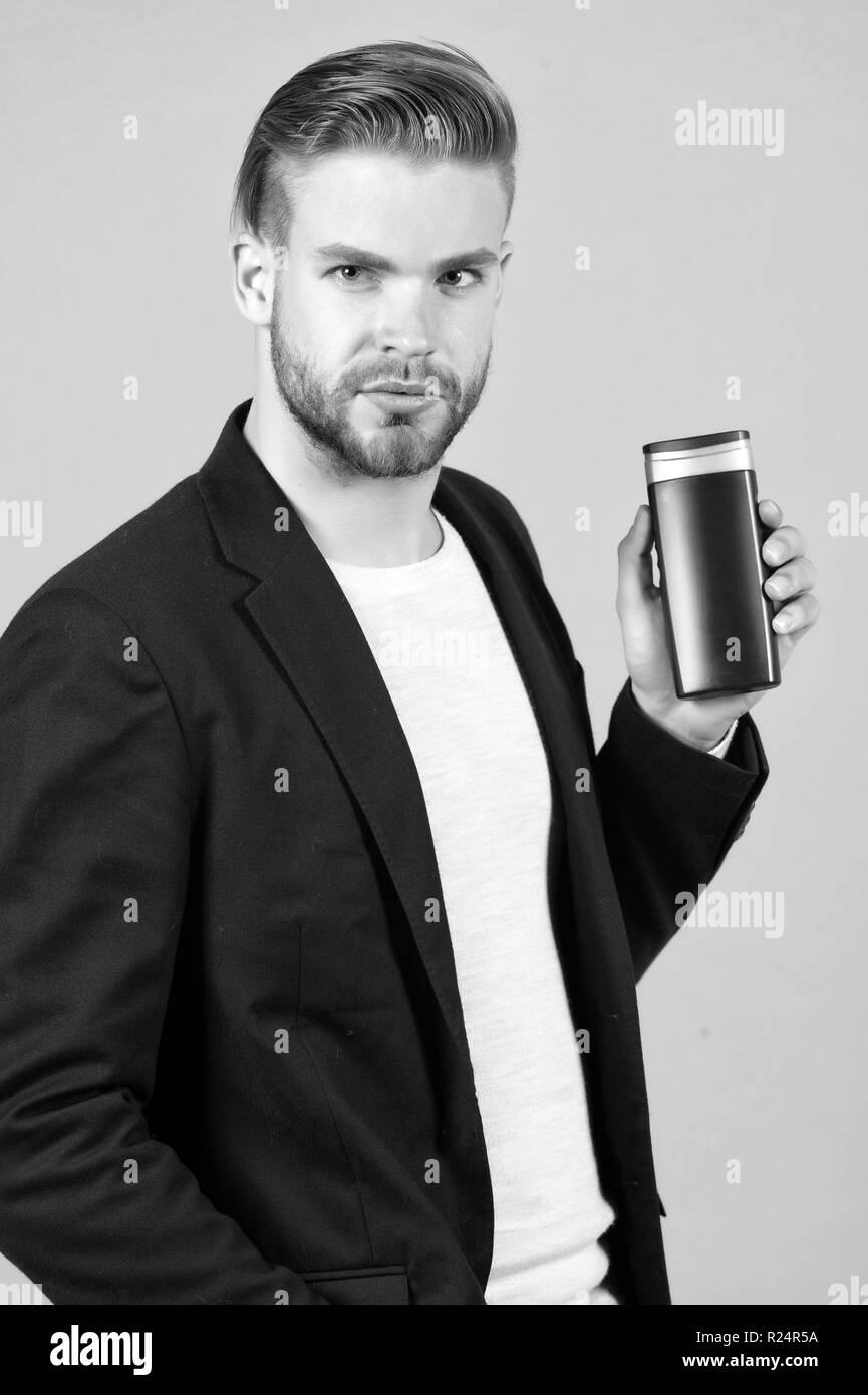 Bearded man hold gel tube. Businessman with shampoo bottle. Hair care and skincare. Health and healthcare. Morning grooming at hairdresser salon or barbershop. Bodycare cosmetic for bath or shower. - Stock Image