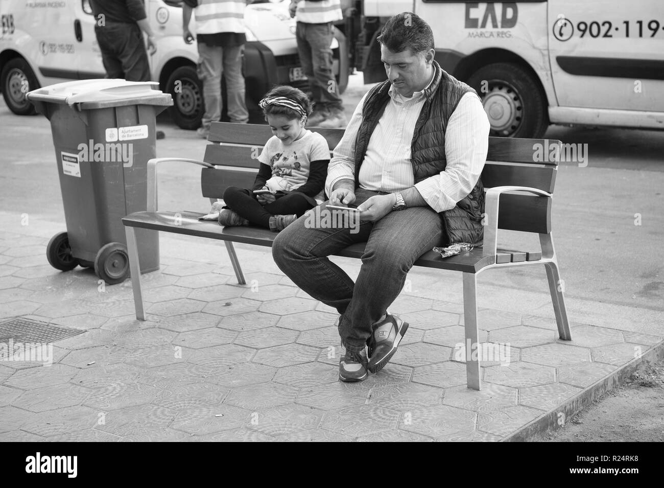 Barcelona, Spain - March 30, 2016: Father man and little girl search in smartphones sitting on bench on city street. Modern life. New technology. Summer vacation and wanderlust. - Stock Image
