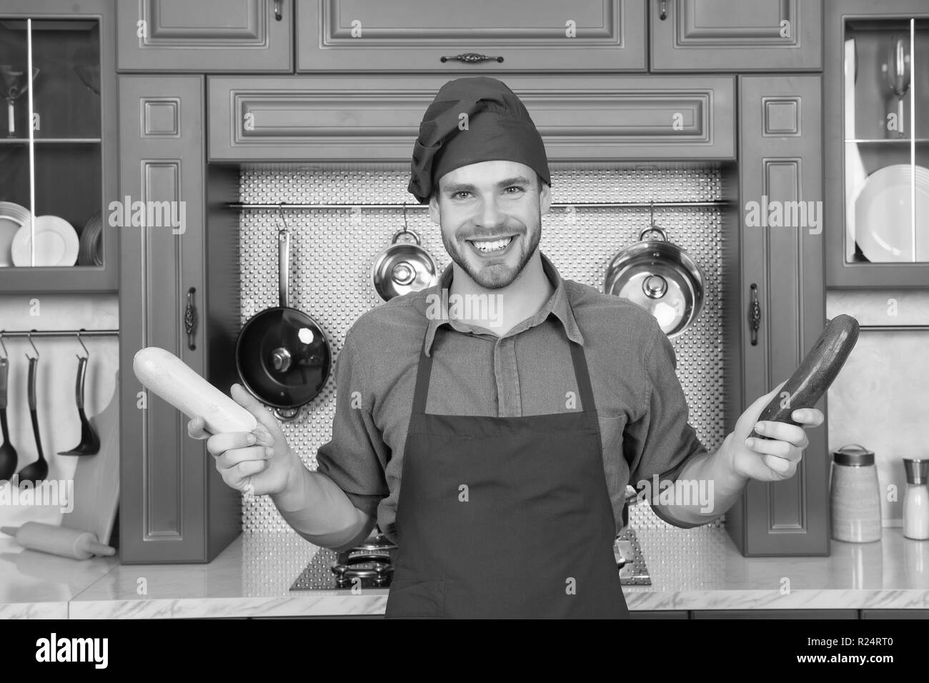 Substitute carefully. Although substitutions seem obvious they can be tricky business. Ruined dish is waste of time. Man chef substitutes marrow with zucchini. Chef smiling knows kitchen tricks. - Stock Image