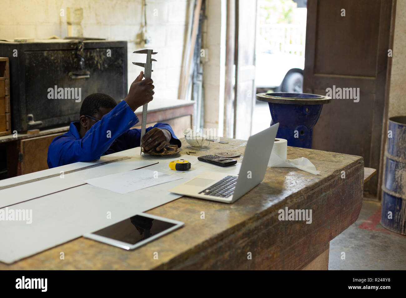 Worker using vernier caliper in foundry workshop - Stock Image