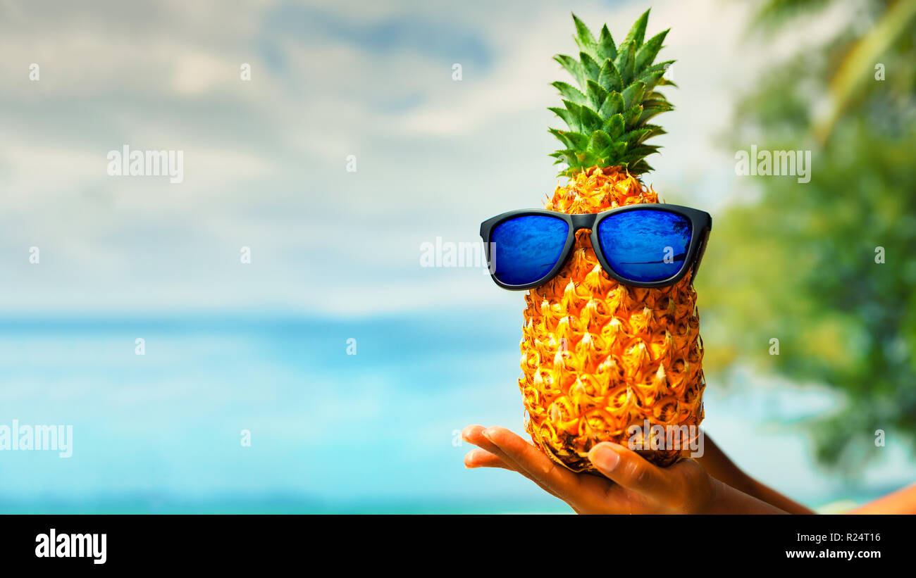 fbfe44d8393bc Funny pineapple fruit in sunglasses on the background nature landscape