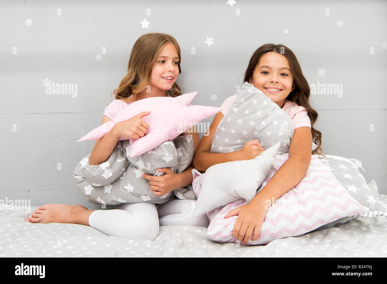 Girls kids hug cute pillow. Cute kids pillows they will love to cuddle. Find decorative pillows and add fun to room. Happy childhood cozy home. Adorable cushions for your child room. - Stock Image