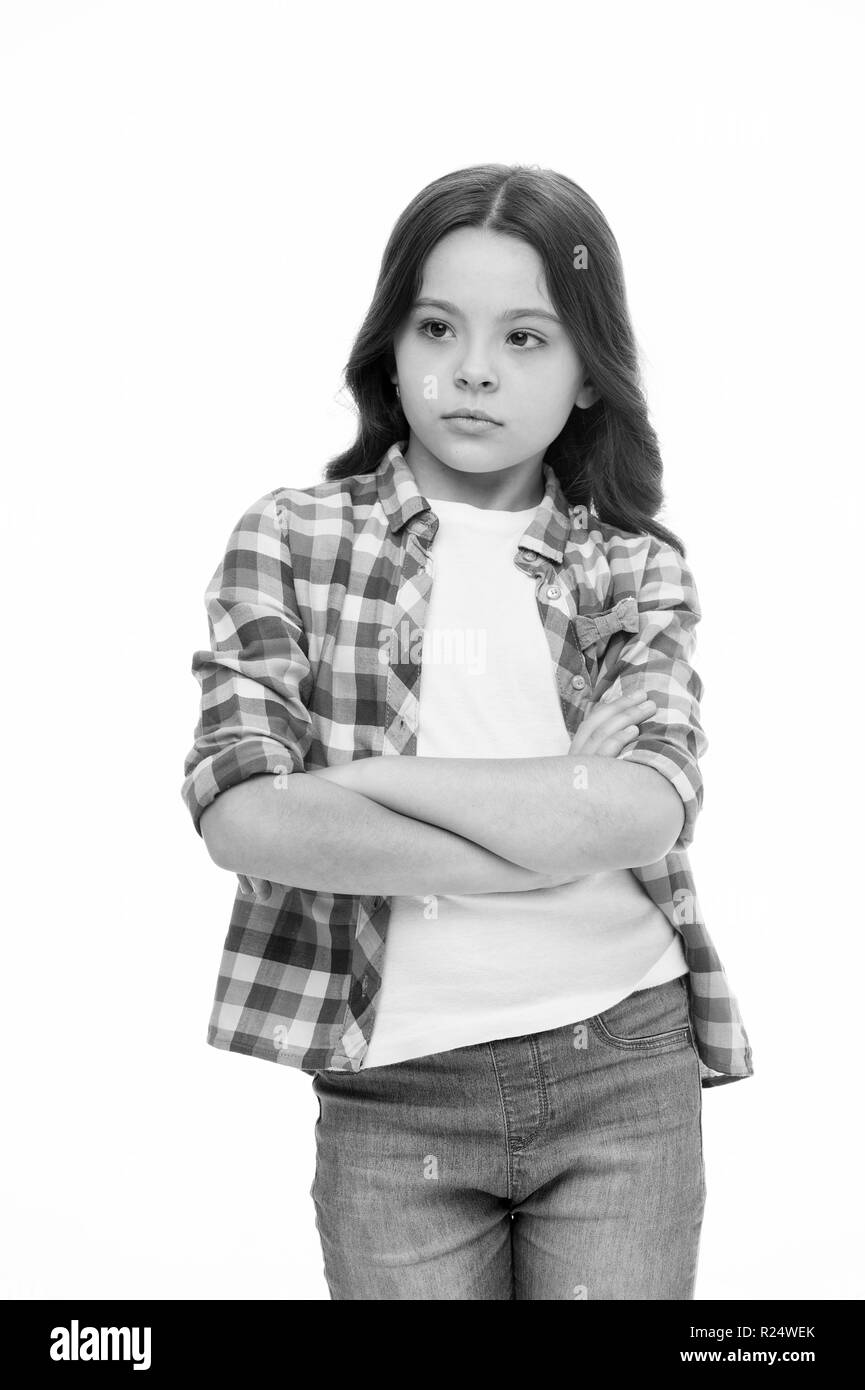 Offended feelings. Child offended keep silence. Girl serious face offended white background. Kid unhappy looks strictly. Girl folded arms on chest looks serious. Sensitive girl not want to talk. - Stock Image