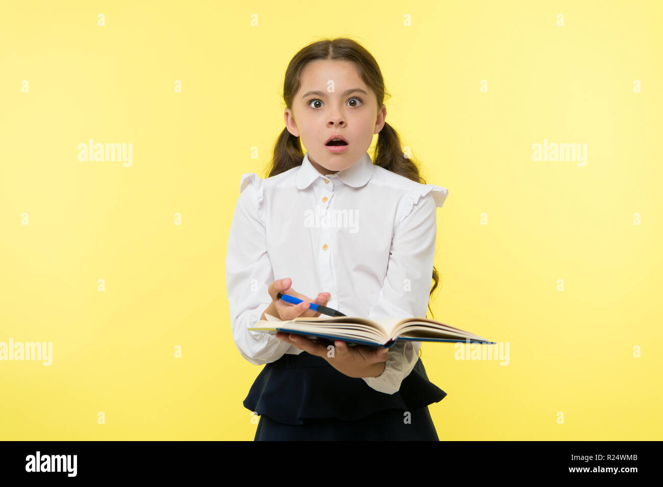 46088b1e3aef Girl cute schoolgirl in uniform hold book with information yellow background.  Pupil get information from book. Child wear school uniform prepare for  lesson ...
