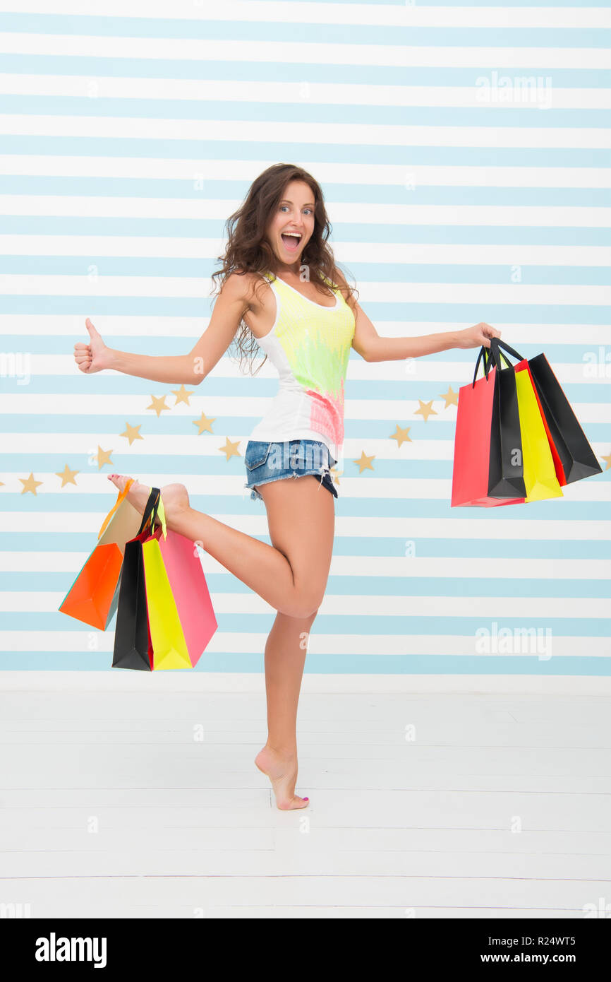 Woman carries bunch shopping bags striped background. Finally bought favorite brand. Tips shop sales. Girl satisfied shopping. Profitable purchase black friday. Too many packages to hold by only hand. - Stock Image