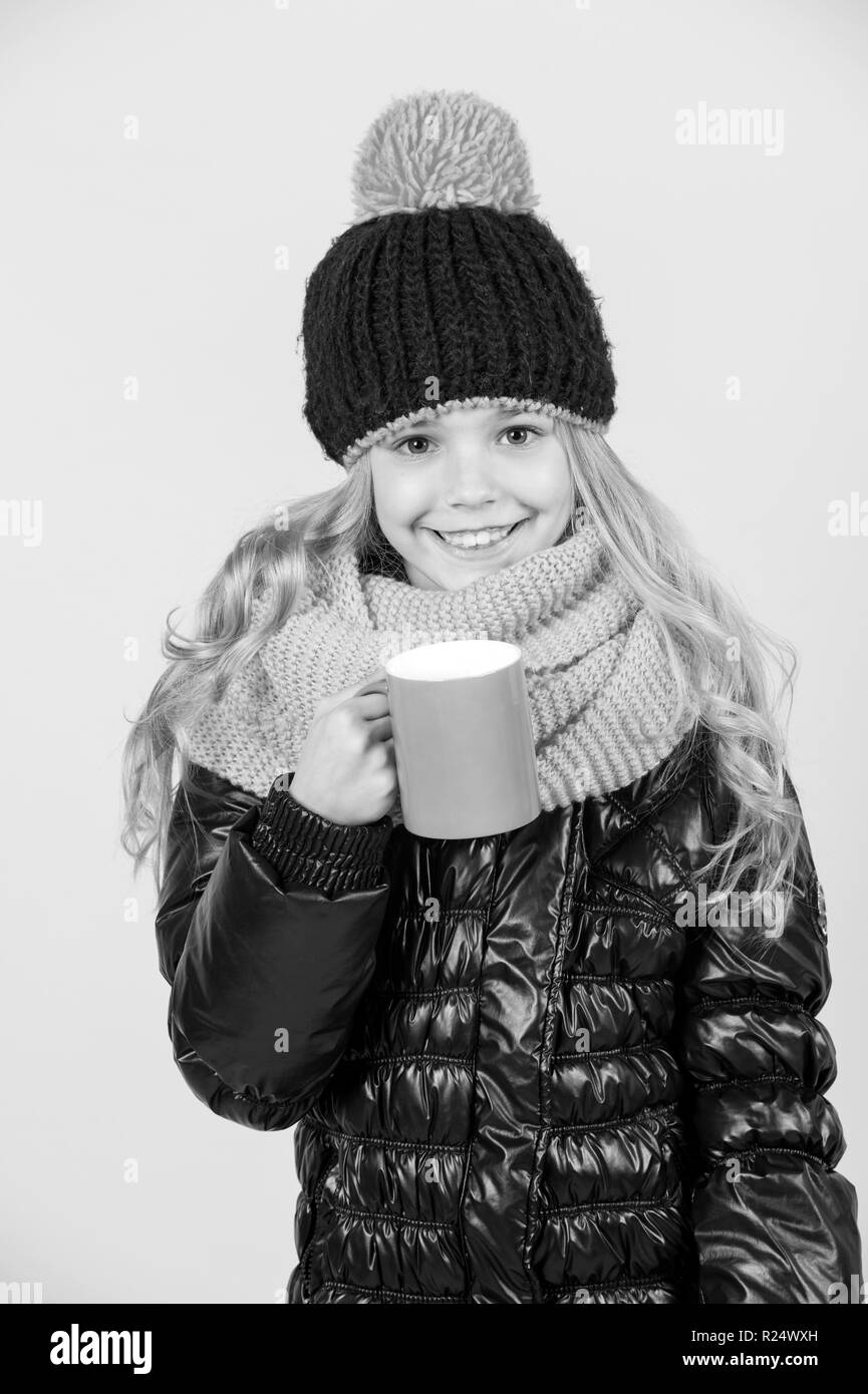 Hot drink in cold weather. Child with blue cup smile on orange background. Tea or coffee break. Girl in hat, pink scarf, black jacket with mug. Autumn season relax concept - Stock Image