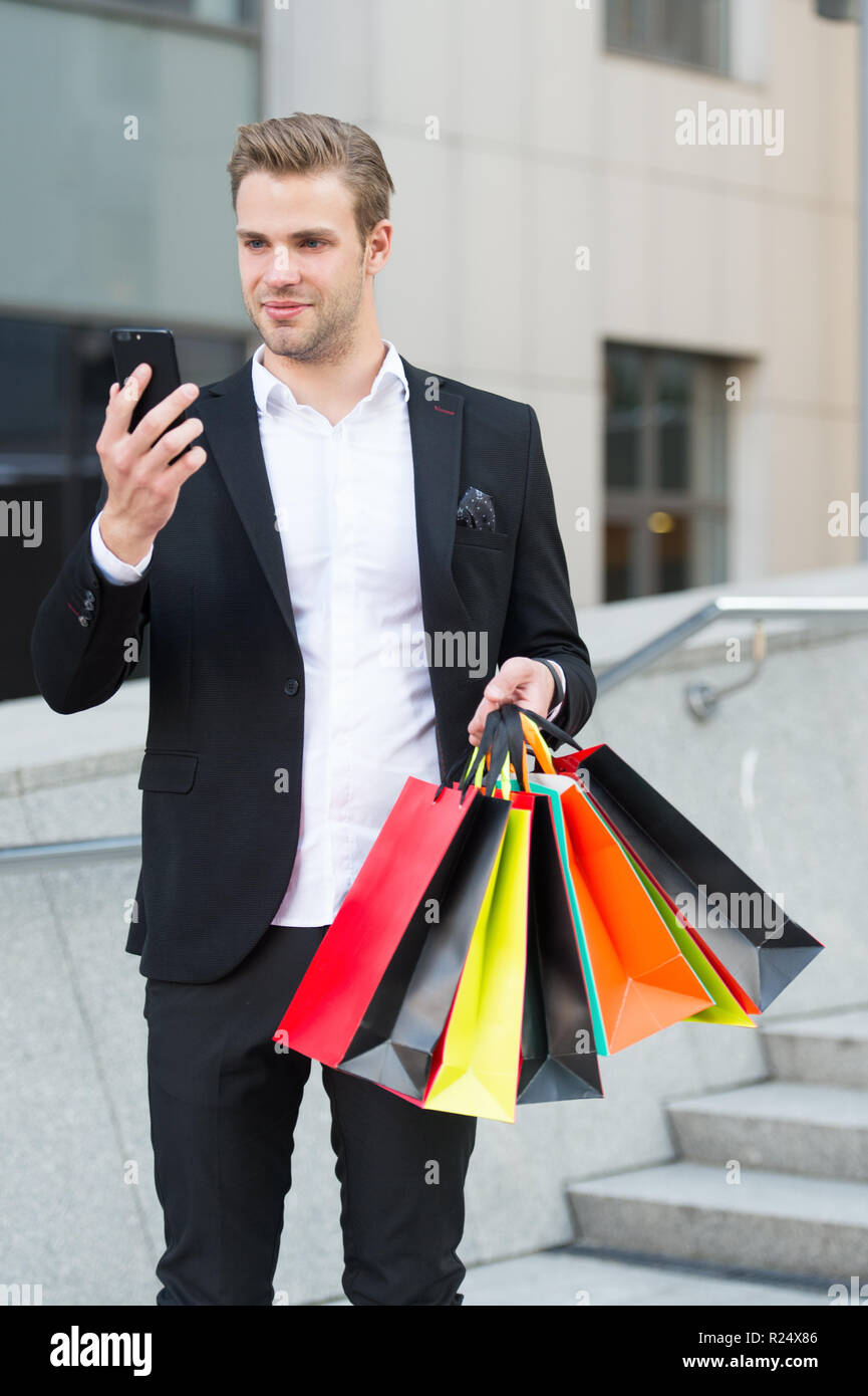 Man hold bags while check discount online with smartphone. Guy carry bunch shopping bags. Profitable deals shopping on black friday. Man hold paper bags after shopping. Black friday discount concept. Stock Photo