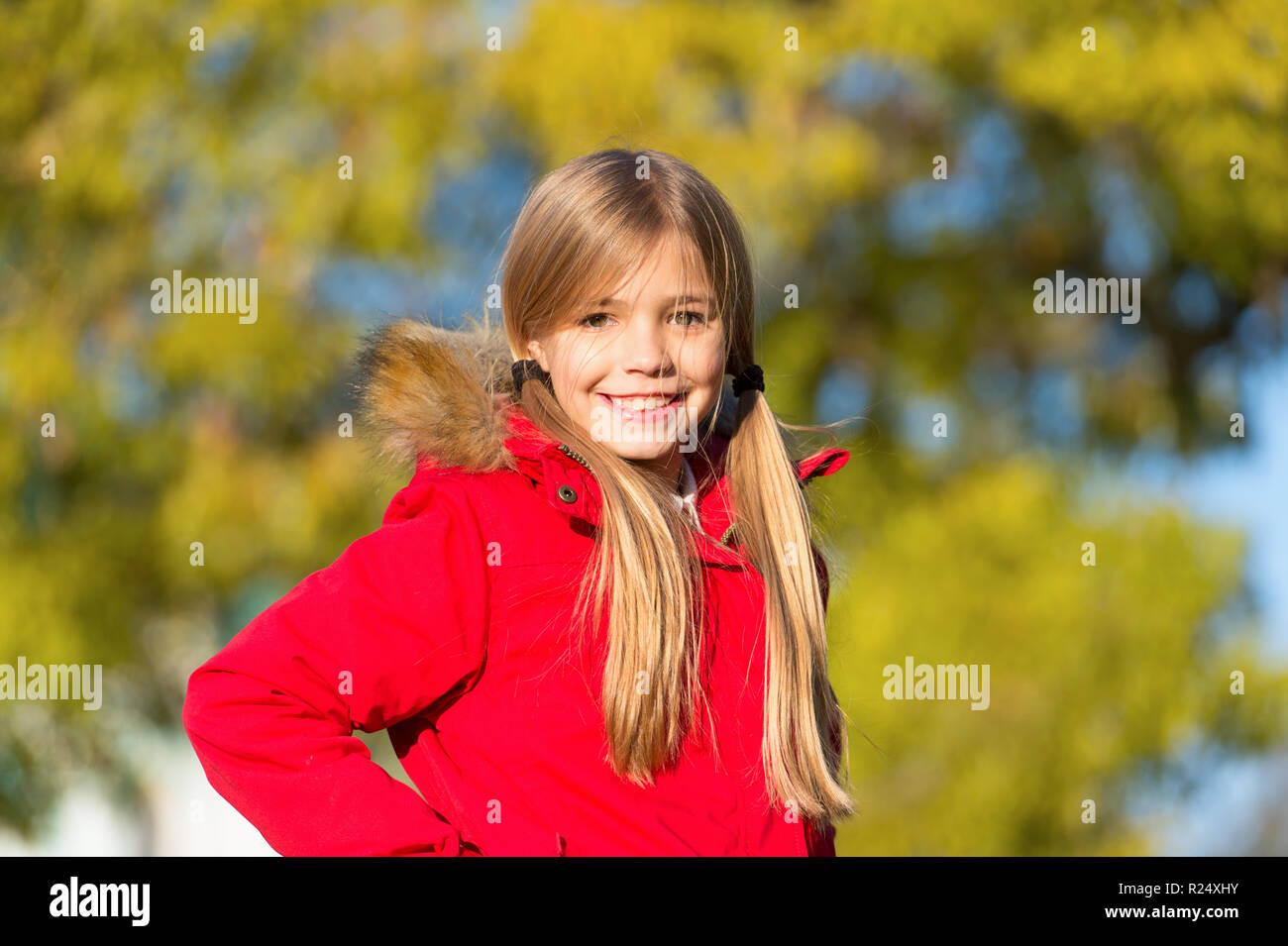 Happy small girl take pleasure in weekend break. Small girl happy smiling enjoy during autumn season. Live life like a long lost weekend. The reds and browns of the wood in autumn. - Stock Image