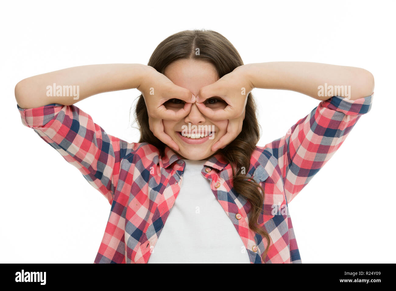 Girl holding fingers near eyes like glasses mask superhero or owl. Play game with mask superhero. Child cheerful mood happy grimace with mask. Pretend be fantastic hero. Kid hide face finger mask. - Stock Image