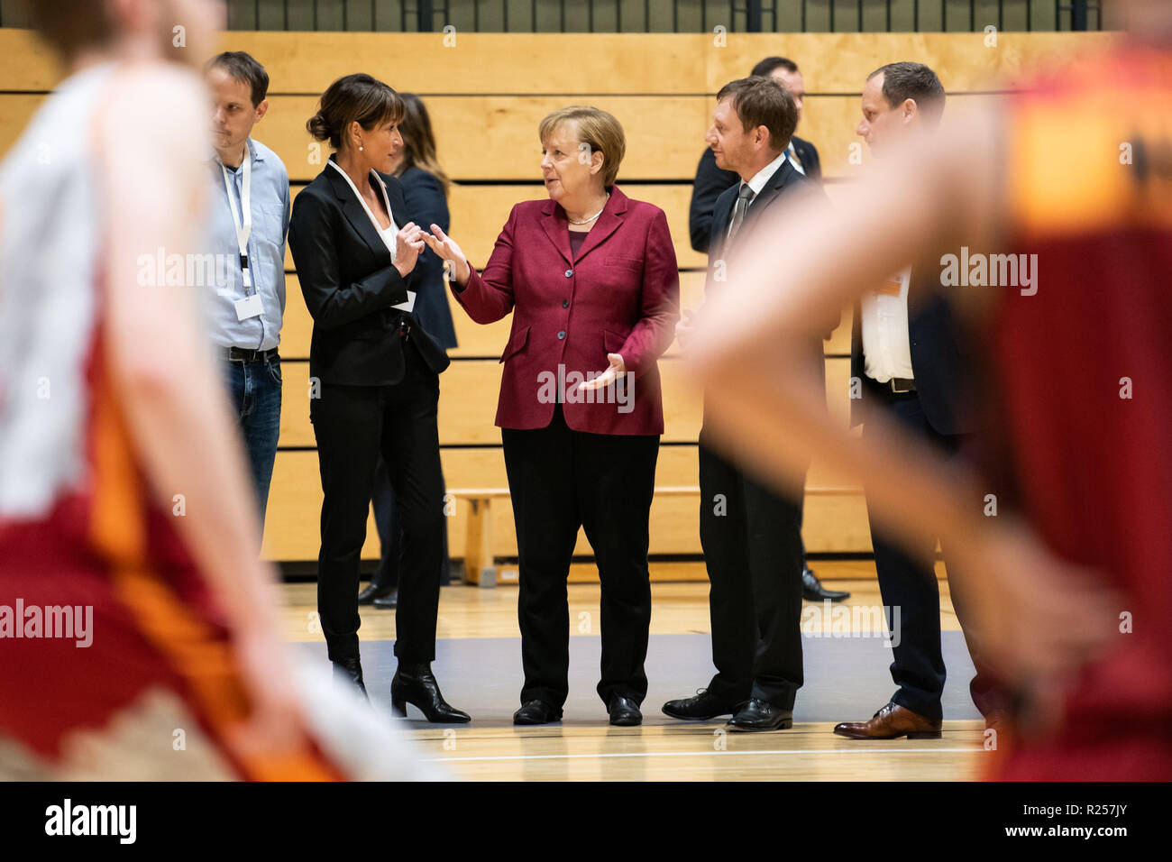 Chemnitz, Germany. 16th Nov, 2018. German Chancellor Angela Merkel (C) visits the basketball club Niners Chemnitz in Chemnitz, eastern Germany, on Nov. 16, 2018. Angela Merkel on Friday clarified her refugee policy during her visit to Chemnitz, a place regarded as the center of several severe xenophobic protests months ago. Credit: Kevin Voigt/Xinhua/Alamy Live News - Stock Image