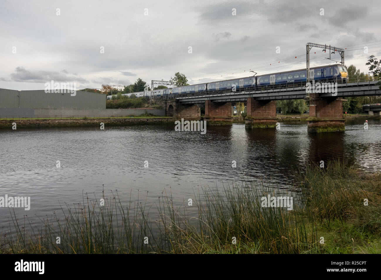 Dumbarton, Scotland, UK - September 28, 2017: A Scotrail passenger train crosses the River Leven at Dumbarton on the North Clyde Line near Glasgow. - Stock Image