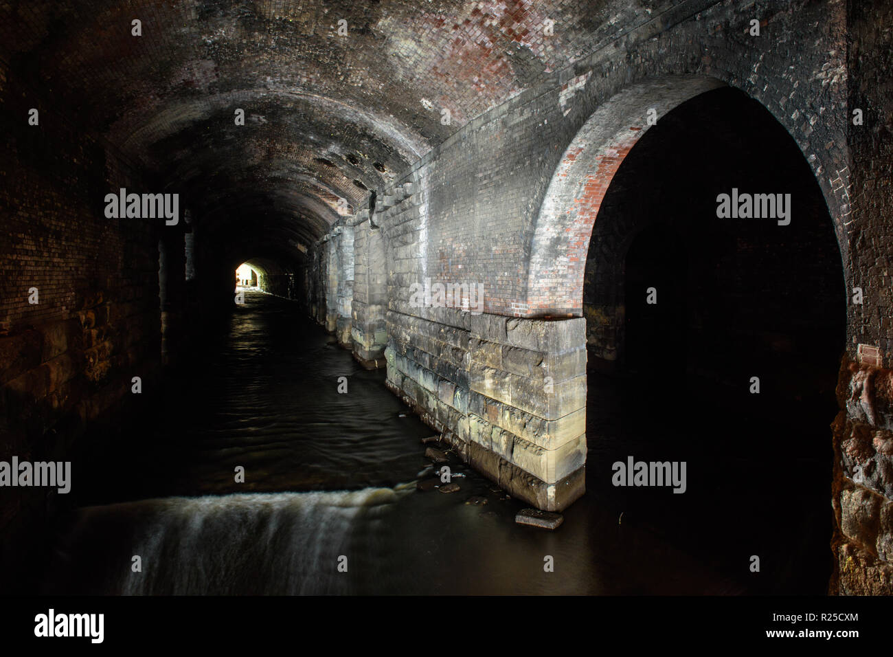 The River Aire runs through tunnels under Leeds Railway Station in Yorkshire. Stock Photo
