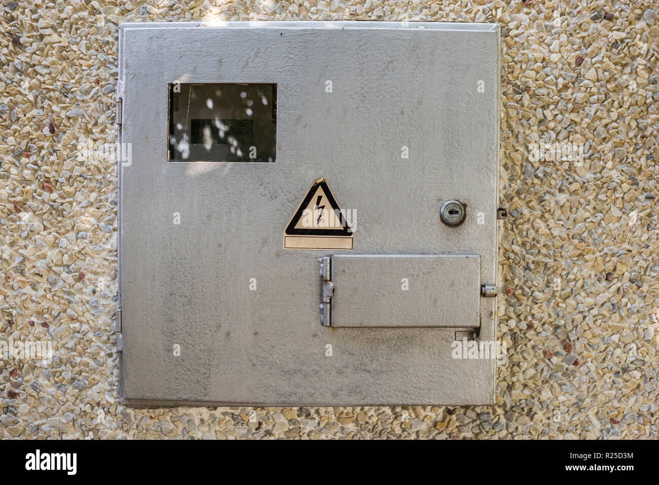 Close-up of locked electrical metal light blue meter box with warning caution sign outside on exterior house wall. Measurement tool and energy saving  - Stock Image