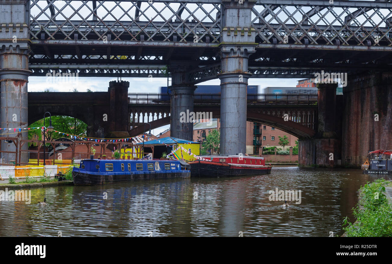 Manchester, England, UK - June 5, 2012: A container freight train crosses Castlefield Basin, where traditional narrowboats are moored on the Bridgewat - Stock Image