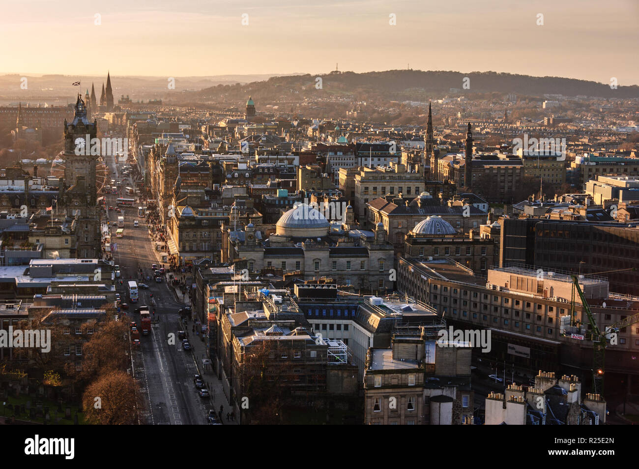 Shops and hotels at lit up by the winter evening sun on Princes Street in Edinburgh's Georgian New Town. - Stock Image