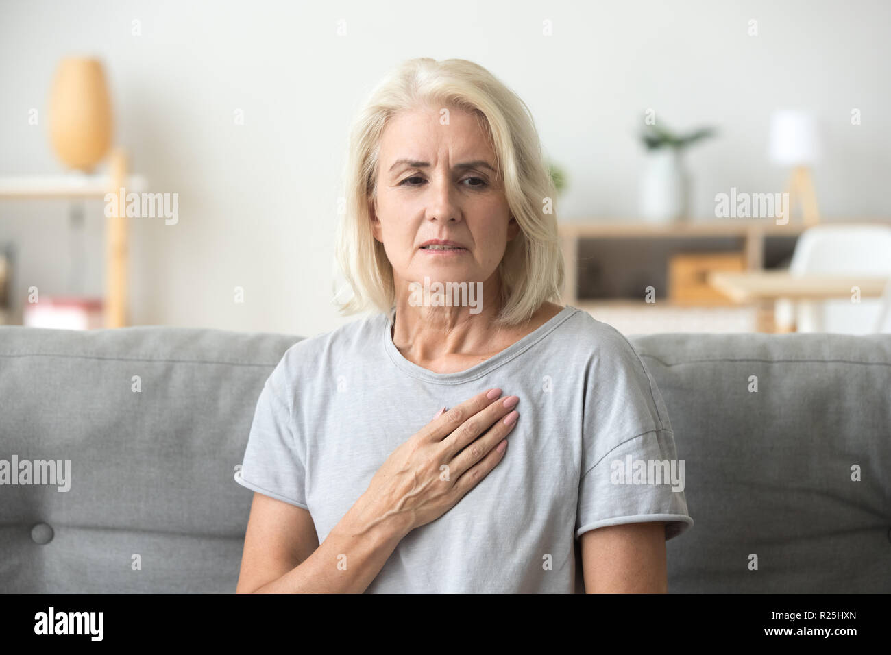 Upset stressed mature older woman feeling heartache touching che - Stock Image
