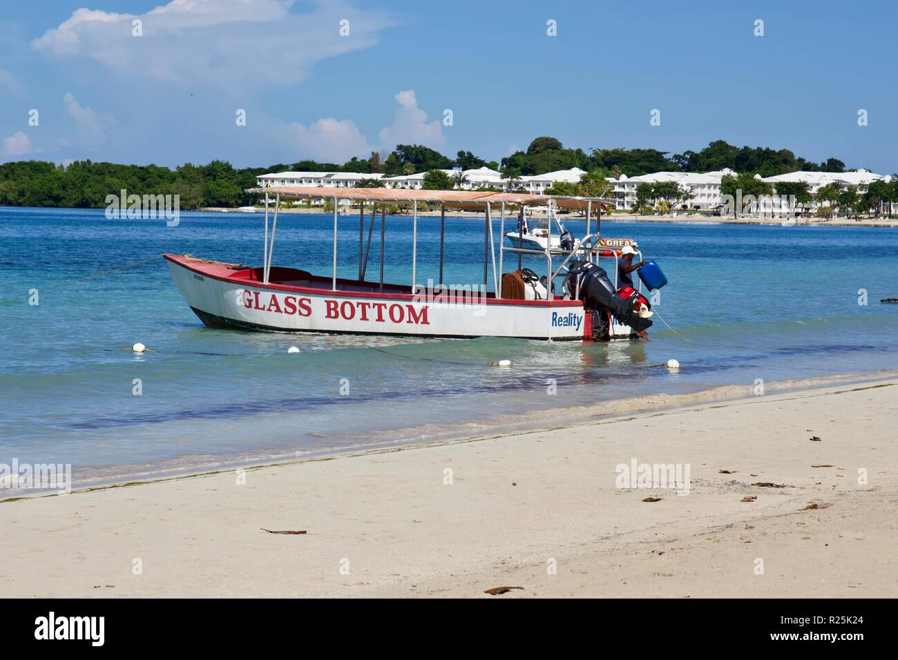 A glass bottom tourist boat on the Seven mile beach in Negril, Jamaica - Stock Image
