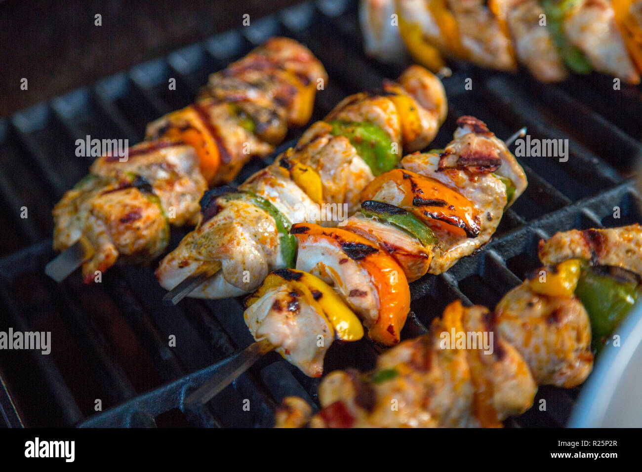 Meat and vegetables skewers on a grill, poultry meat and pepper pieces on a skewer, are grilled, - Stock Image