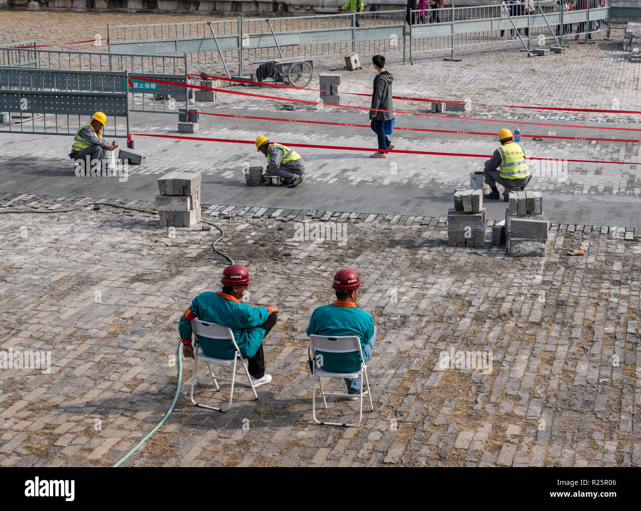 Supervisors oversee repair of paving slabs in Forbidden City - Stock Image