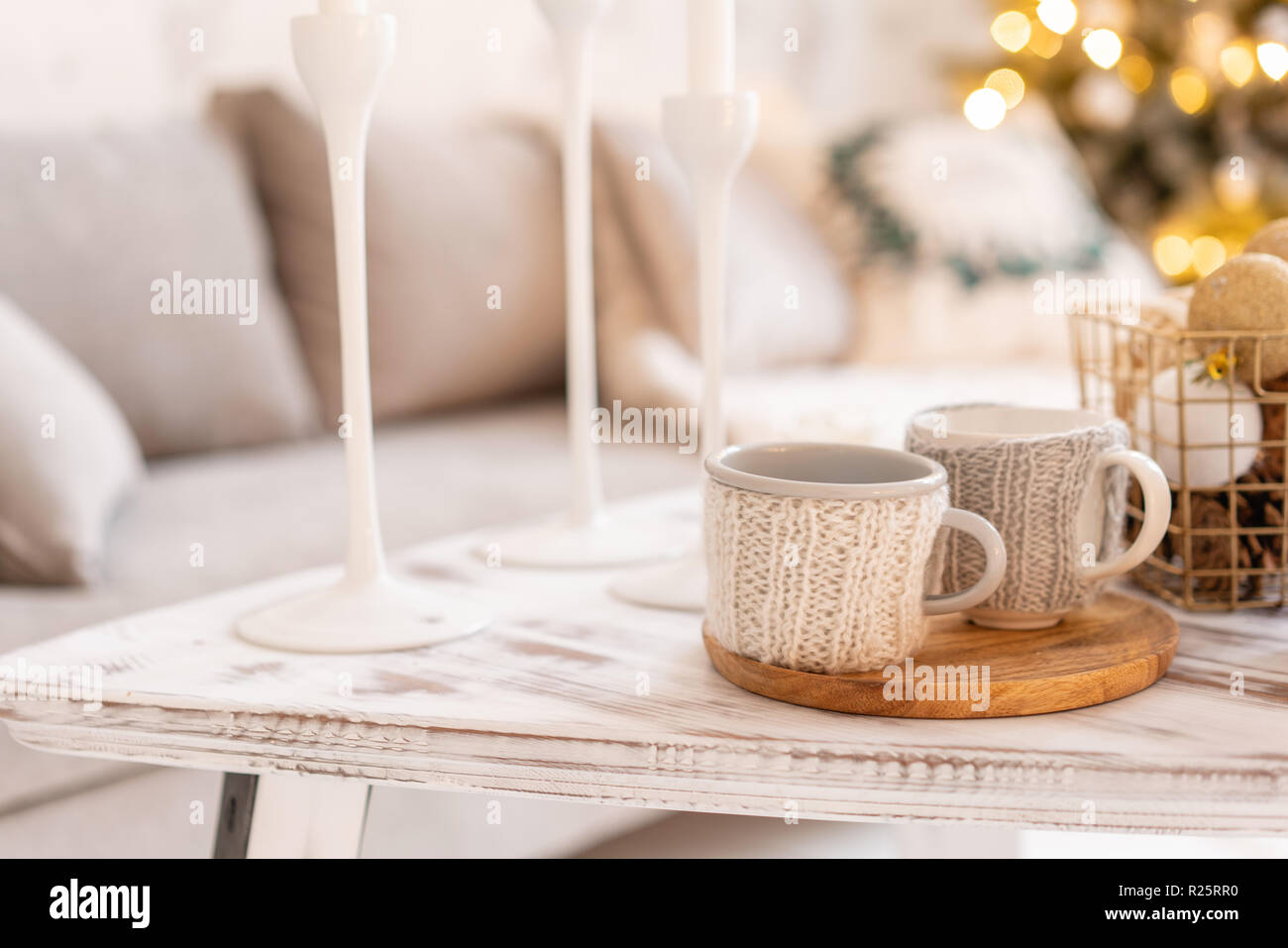Knitted woolen cups on a wooden table. two cups of hot coffee. the concept of heat. holidays and events. Autumn and winter, leisure concept. Cozy, comfy, soft. - Stock Image