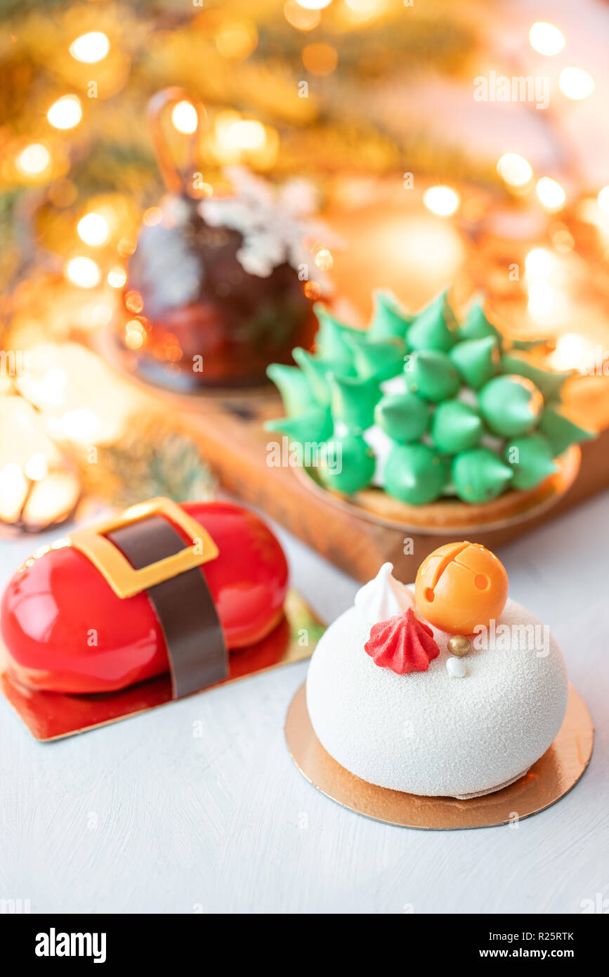 Mini mousse pastry desserts covered with velour or glaze. Garland lamps bokeh on background. Modern european cake. French cuisine. Christmas theme. - Stock Image