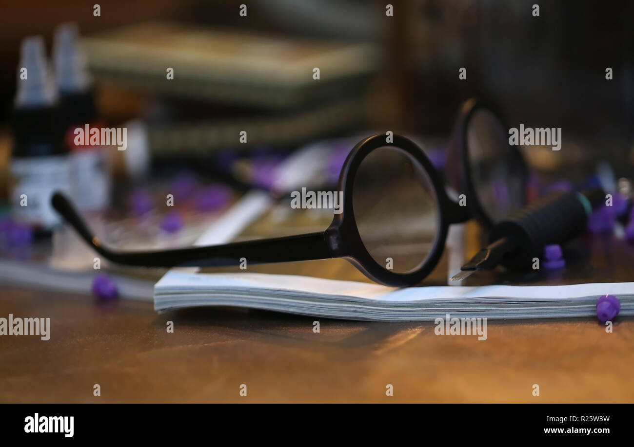Old spectacle in a wooden table as working concept - Stock Image
