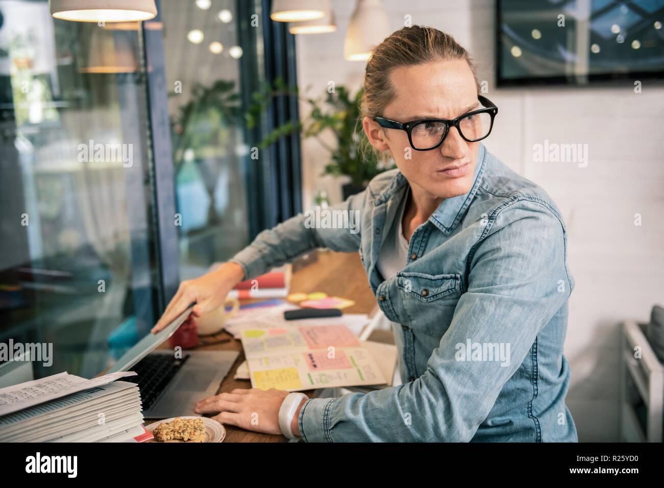 Unhappy cheerless young man closing his laptop - Stock Image