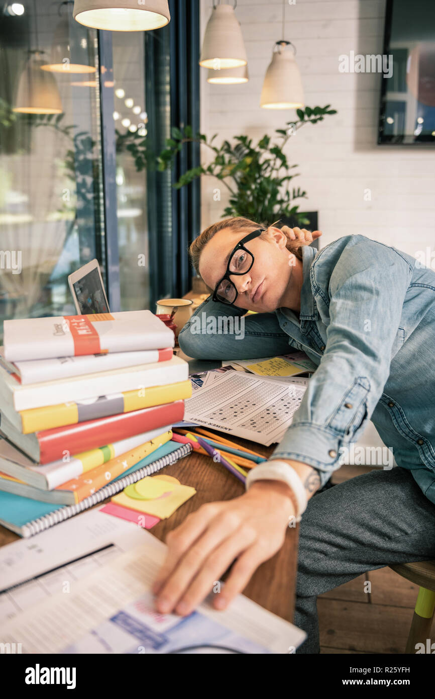 Serious young student being surrounded by books - Stock Image