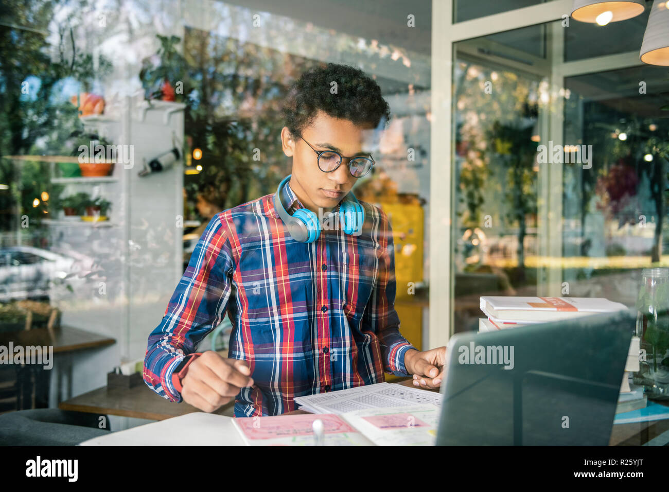 Serious young boy focusing on his school task - Stock Image