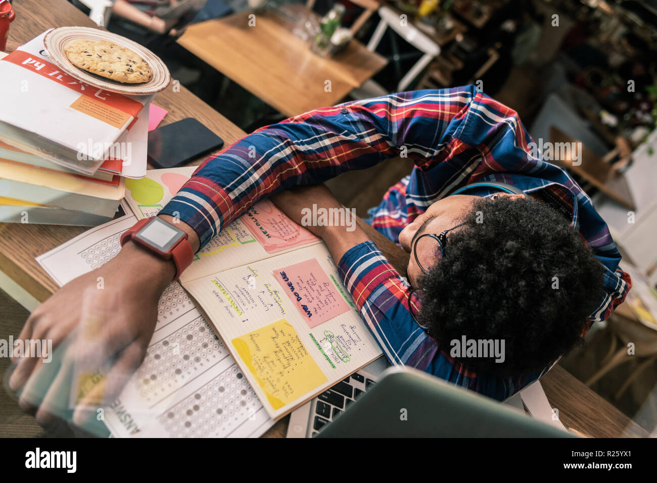 Pleasant young man sleeping on the desk - Stock Image