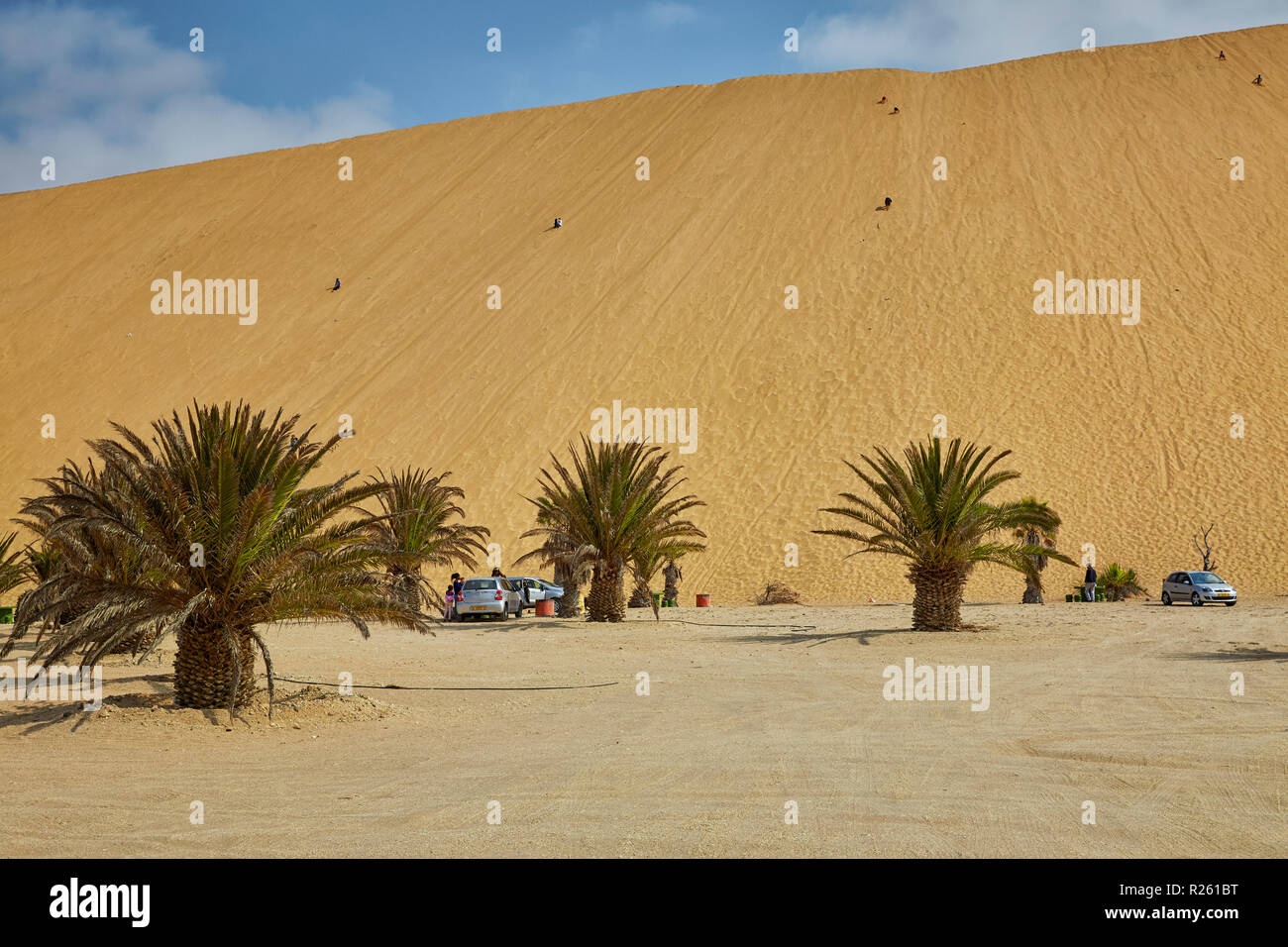 People climbing Dune 7 in Walvis Bay in Namibia, Africa - Stock Image