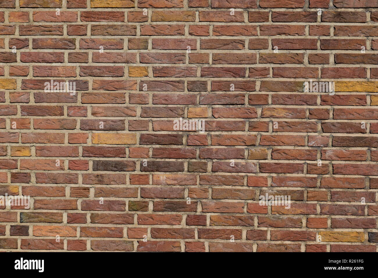 Old red brick wall showing signs of age and decay mortar. - Stock Image