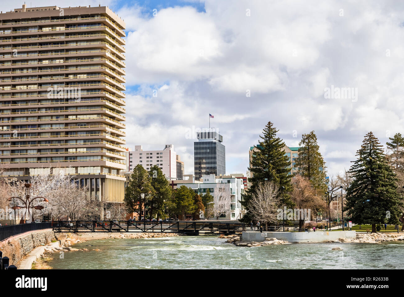 Reno, Nevada skyline as seen from the shoreline of Truckee river flowing through downtown; - Stock Image