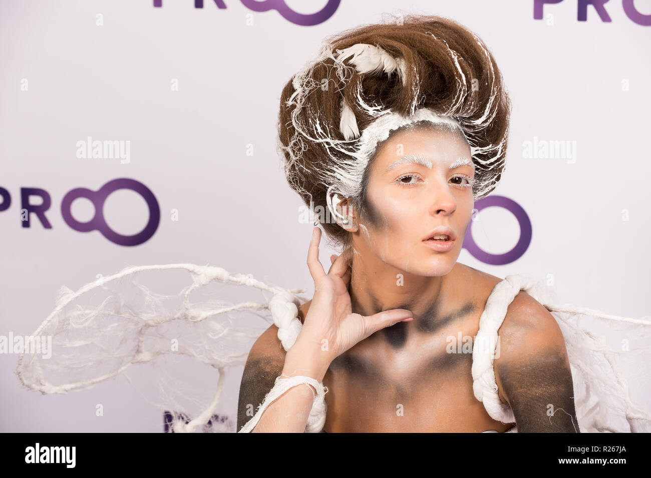 Kyiv, Ukraine - September 16, 2015: girl model with hair performs professional makeup and body art on masterclass at International exhibition of perfumery and cosmetics Intercharm as animal in white - Stock Image