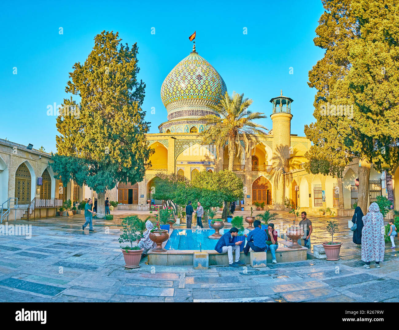 SHIRAZ, IRAN - OCTOBER 12, 2017: The courtyard of Imamzadeh Ali Ibn Hamzeh Holy Shrine with small garden, fountain and beautiful Persian architecture, - Stock Image