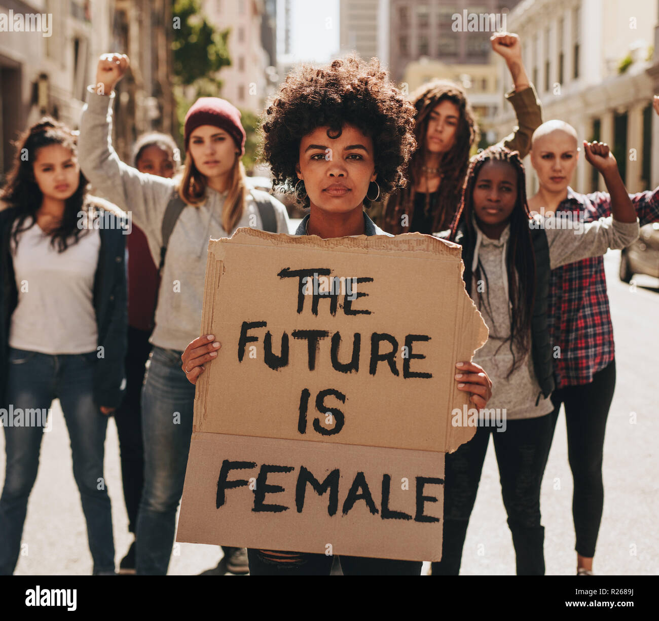 Protesters hold up signs of the future is female. Group of female protesting outdoors for women empowerment. - Stock Image