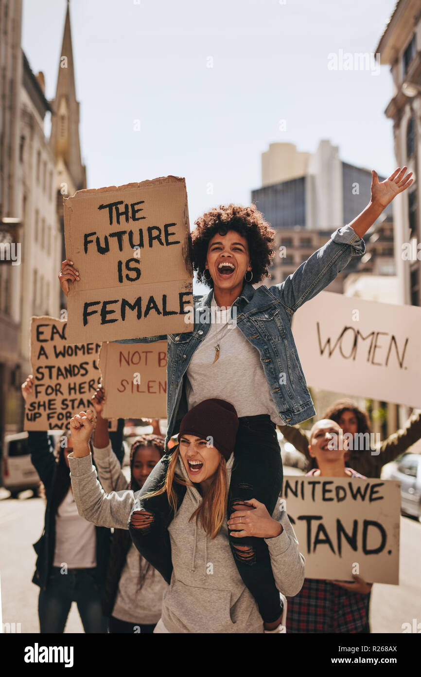 Female protesters marching on the road with placards. Group of women protesting outdoors on road. - Stock Image