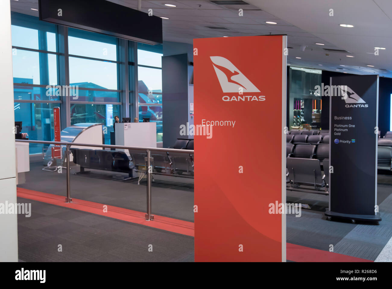 A Qantas departure lounge waiting area for people to congregate before boarding a flight. Economy passengers use a separate line to other classes. - Stock Image