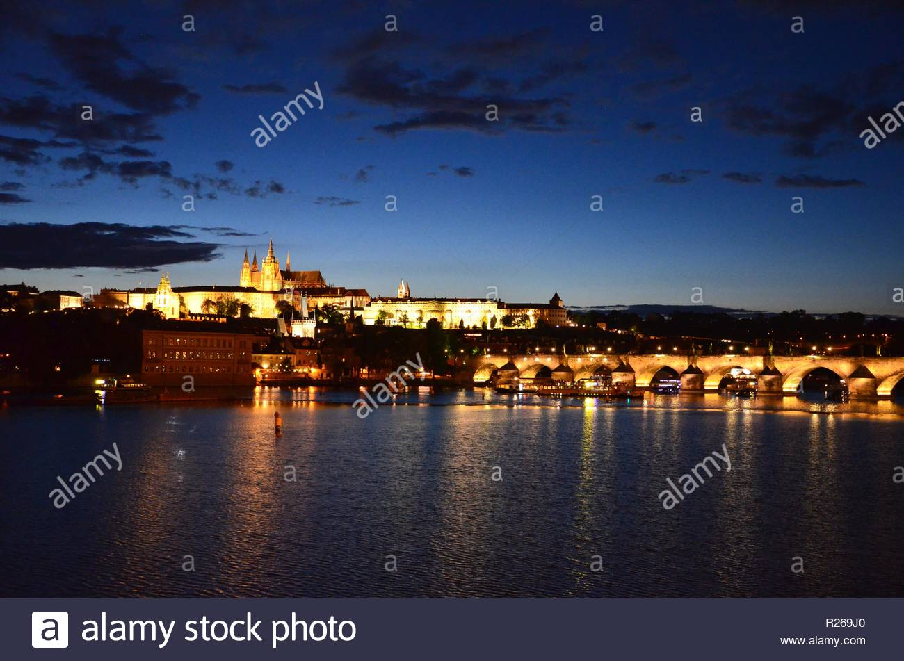 Illuminated Charles Bridge and Castle in Prague at night, reflections in water of River Moldau - Stock Image