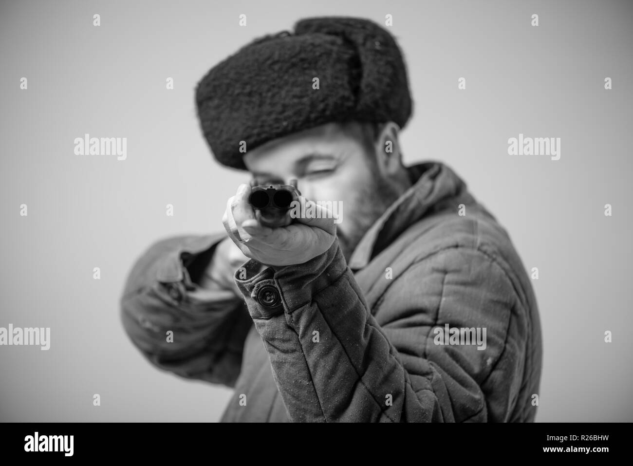 Concept - take target. Hunter with horizontal double-barreled shotgun in hands, rifle is directed forward, retro style, studio shot Stock Photo