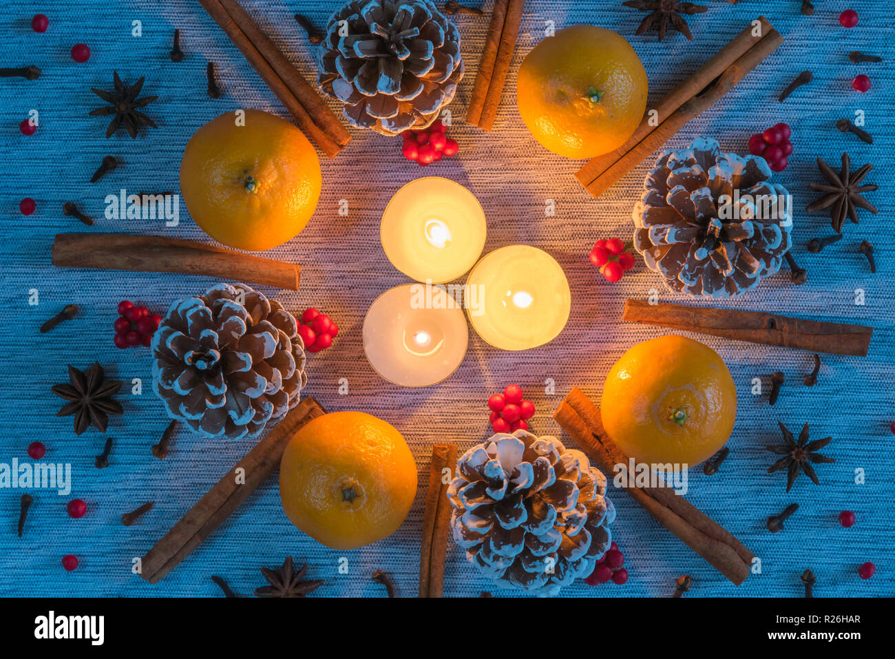 Christmas arrangement of candles surrounded by wreath of pinecones, oranges, cinnamon sticks - Stock Image